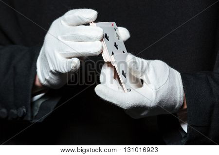 Closeup of hands of man magician in white gloves shuffling playing cards over black background