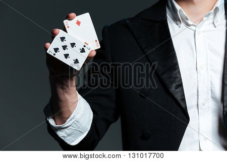 Closeup of man magician with two playing cards in his hand over grey background