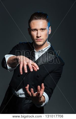 Handsome young man magician showing tricks over grey background