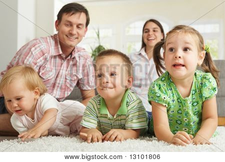 Family at home: happy children with their parents lying on floor making faces.