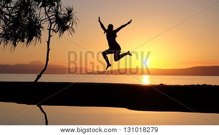 Girl jumping at the waterpool on the beach against the sunset at Balicasag island of Philippines