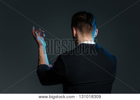 Back view of young man magician standing with raised hand over grey background
