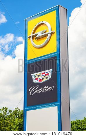 SAMARA RUSSIA - MAY 22 2016: Cadillac and Opel logo on a sign outside the car or automotive dealership against the blue sky
