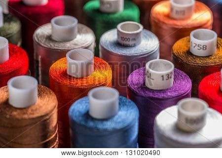 Sewing threads multicolored background close up, spools