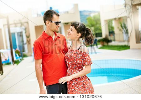 couple standing near the pool. man wearing in red polo shirt and sunglass.