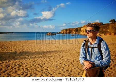 man standing at the sea on the beach. man wearing in blue shirt and sunglass