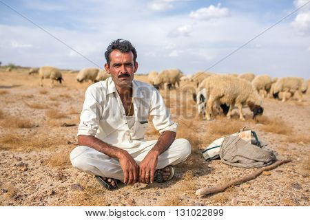 Jaisalmer, India - March 13, 2016: Portrait of unidentified rajasthani shepherd with his sheeps outside of Jaislamer, Rajasthan, India