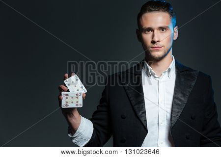 Serious young man magician standing and holding two playing cards over grey background