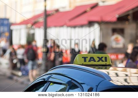 the yellow symbol or sign with an inscription of a taxi is located on a car roof on an indistinct background street and blank space