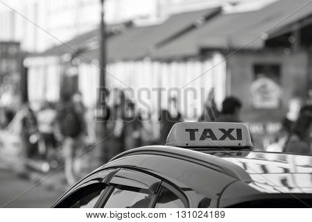 symbol or sign with an inscription of a taxi is located on a car roof on an indistinct background street of monochrome color