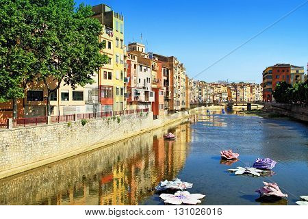 GIRONA SPAIN - MAY 10 2015: Flowers and house's reflection in Onyar River Each spring, during the 2nd week of May, the streets of Girona fill with colour as the city hosts it's annual flower festival Girona Temps de Flors. The festival takes place in the