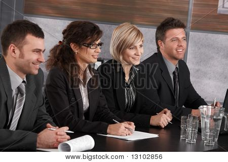 Businesspeople sitting at conference table on business seminar, smiling.
