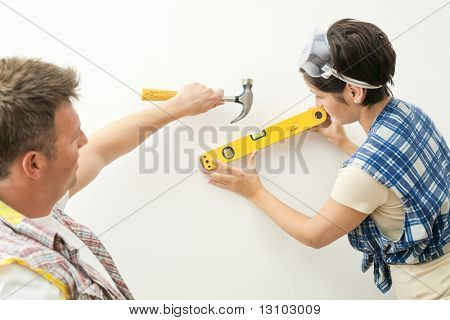 poster of Couple working together on home renovation, woman holding spirit level tool, man holding hammer.