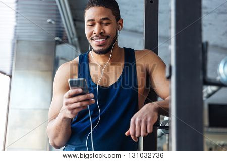 Smilling fitness man using smartphone with earphones in the gym after workout