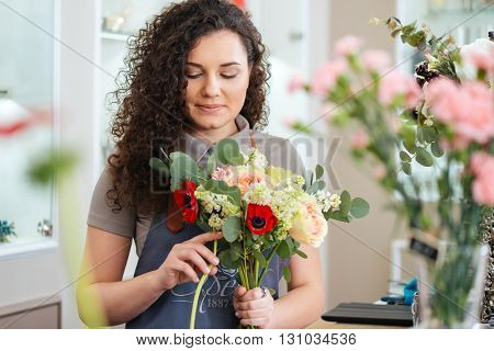 Thoughtful cute young woman florist holding flowers and making bouquet in shop