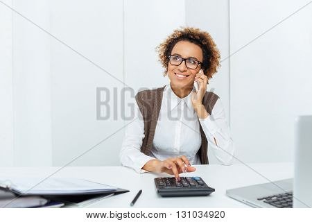 Cheerful african american young woman accountant using calculator talking on mobile phone on workplace
