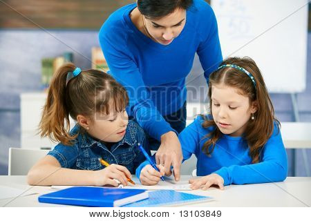 Elementary age children listening to female teacher in school classroom.