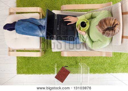 Woman using laptop, drinking coffee, sitting in armchair with legs up on footboard in overhead view. poster