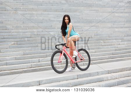 Sexy girl on bicycle. Young slim sexy sporty woman in blue shorts and white snickers long-haired, sensual posing on pink fix bicycle at grey stairs background. Soft toned.