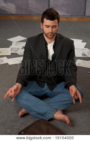 Trendige Büroangestellter sitzend auf Boden, Yoga-Meditation mit geschlossenen Augen, umgeben von Dokumentation zu tun