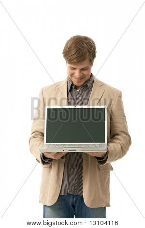 Smiling young man holding laptop computer with blank screen, looking down. Copyspace, cutout.