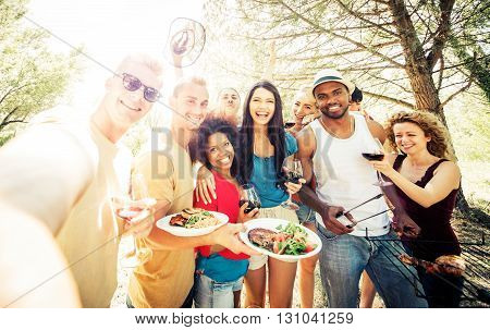 Group of friends making barbecue in the nature. Eating and sharing positive emotions