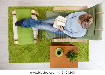 Woman reading book in armchair with crossed feet up on footboard, having coffee, in high angle view.
