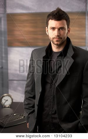 Portrait of young businessman in trendy fashionable jacket standing in office.