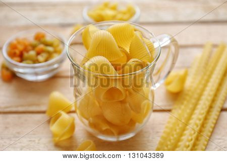 Pipe rigate pasta in cup on wooden table background