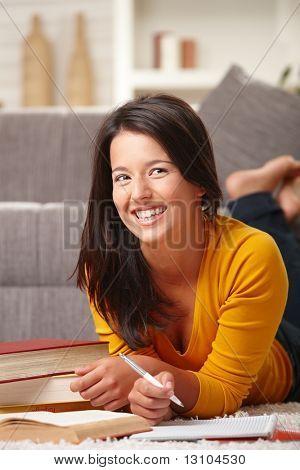 Happy Teen Girl lernen Stock zu Hause mit Büchern und Stift in die hand, lächelnd.