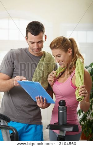 Young woman checking training plan with her personal trainer standing beside exercise bike at home.