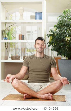 Mann tun Yoga-Übung zu Hause, sitzen im Wohnzimmer im Erdgeschoss.