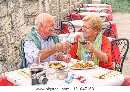 Senior couple drinking and eating in bar outdoor - Man having fun and smiling with her wife in castle restaurant during evergreen vacation - Loving eachothers for entire life concept - Warm filter