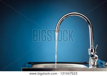 mixer tap with flowing water, blue background