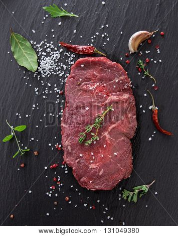 Delicious raw beef steak on black stone table, close-up.
