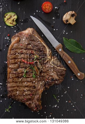 Delicious beef T-bone steak on black stone table, close-up.