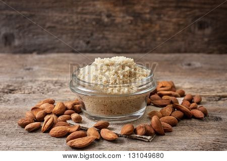 almond flour in a wooden bowl almonds on old wooden background