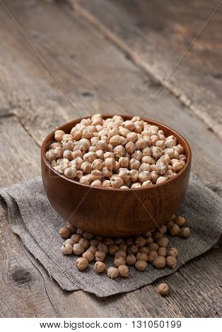 dry chickpeas in a wooden bowl on the old wooden background