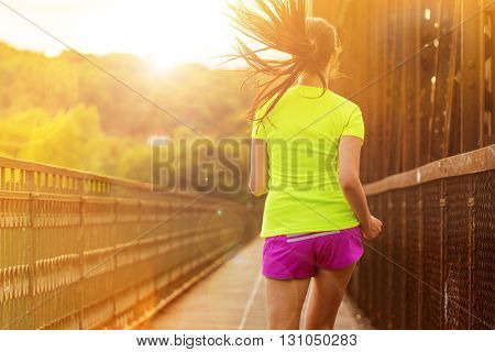 Running woman during sunny day in the city. Female fitness model training outside in Prague.