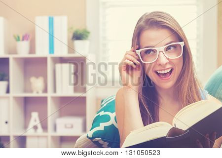 Happy Young Woman Reading A Book On Her Couch