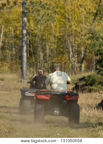 ATV riders on a trail on a autumn day