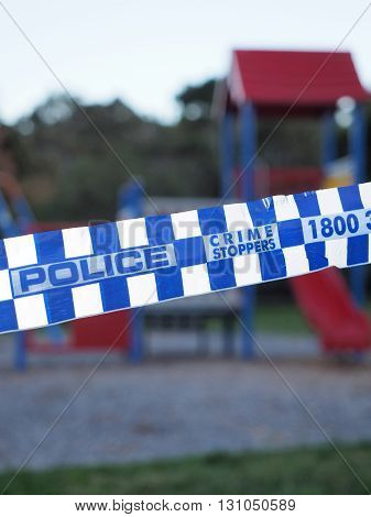 Melbourne, Australia -May 16, 2016: Blue and white Police tape cordoning off an colorful playground area like a crime scene