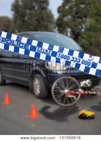 Melbourne, Australia -May 21, 2016: Blue and white Police tape cordoning off a damaged bicyle under a car and like a crime scene