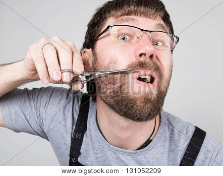 male barber cuts his own mustache, looking at the camera like the mirror. stylish professional hairdresser expresses different emotions.