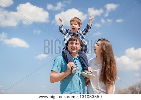 Family of three people, young parents and a little son on a sky background