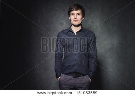 Handsome man posing in black shirt on dark background in studio.