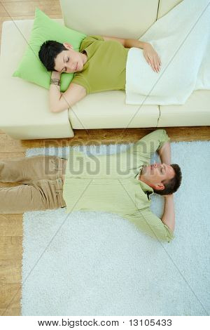 Couple sleeping at home on sofa and on floor. Overhead view.