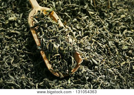 Pile of dry tea with wooden spoon, close up