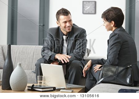 Young business people having meeting at office sitting on sofa talking.