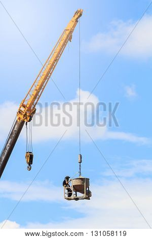 Crane and worker in building construction site